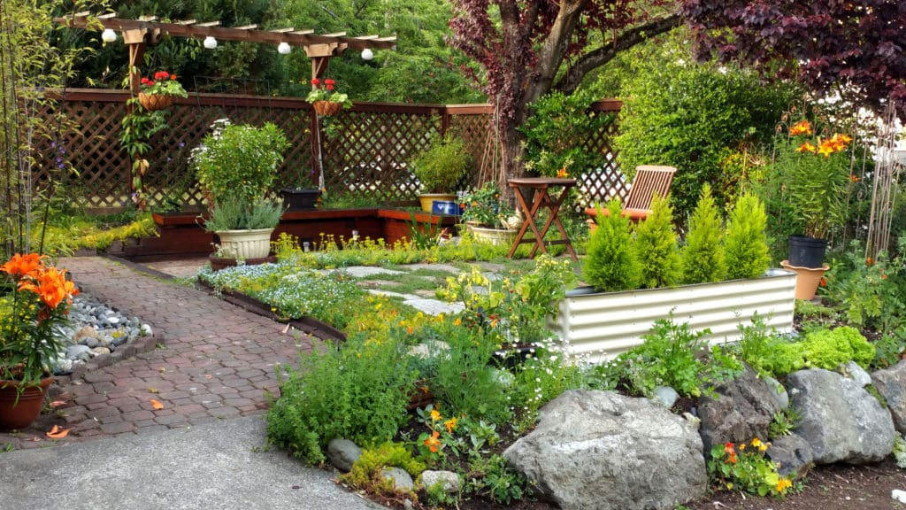 Small patio area surrounded by brick, stones, stepping stones, fencing, latticework, trees and flowering plants.
