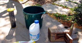 Image of green bucket, bottle of clorox, brush with handle and birdhouse with opened panel