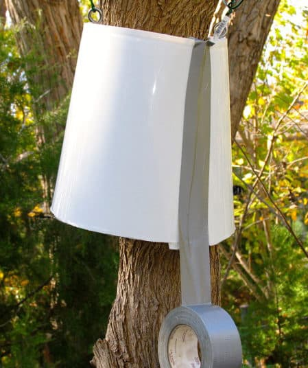 White bucket suspended with wires and around a tree trunk.
