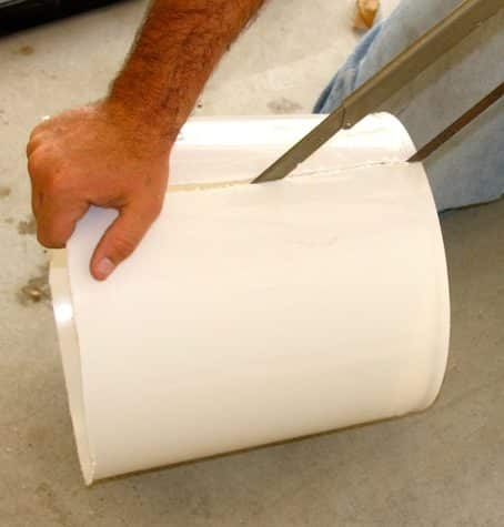 White bucket on its side with hacksaw being used to cut it.
