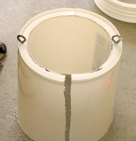 White bucket setting bottom up with an eyebolt on each side.