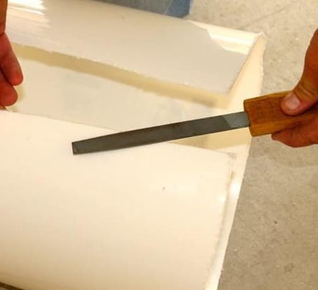 White bucket on its cut side and a file being used to smooth rough edges caused by a hacksaw.