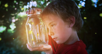 Several fireflies in a jar, with young boy looking at them.